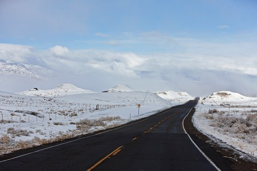 A passing winter storm leaves snow on the ground through which U.S. Highway 64 passes, near Beclabito, New Mexico. : Stock Photo