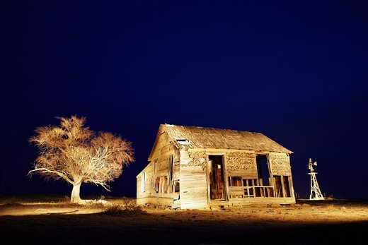 A night view of a decaying farm house, an old  Fairbanks-Morse Eclipse windmill, and a dead tree, on eastern Colorado's plains. : Stock Photo