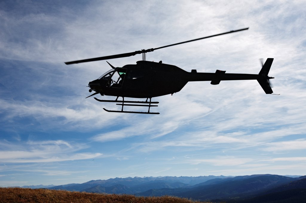 Stock Photo: 4316-3547 Silhouette of a U.S. Army National Guard OH-58 Kiowa in Colorado's Rocky Mountains.