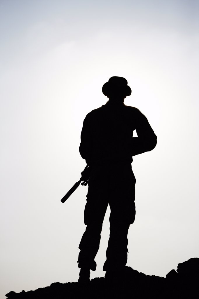 Stock Photo: 4316-3775 Silhouette of a U.S. Marine Holding a Rifle with a Suppressor, at a Small, Remote, Austere U.S. Marine Corps Combat Outpost in Afghanistan's Helmand Province