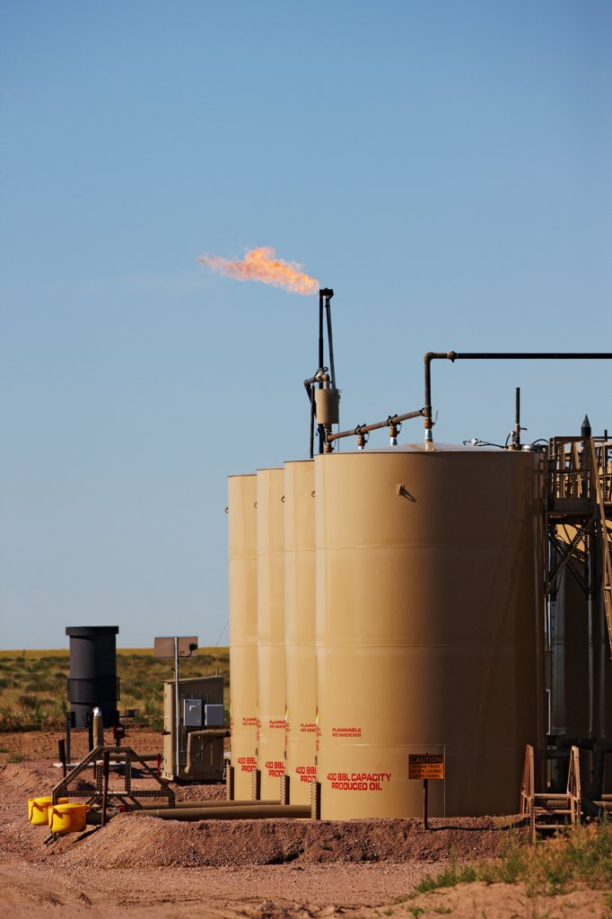 Stock Photo: 4316-4095 A Gas Flare And Crude Oil Storage Tanks