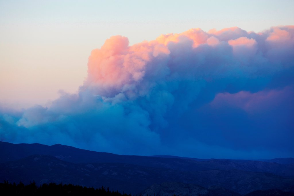 Stock Photo: 4316-4439 Sunset light on plume of smoke from raging mountain wildfire, as seen from 11,000 feet in Colorado's Rocky Mountains, USA