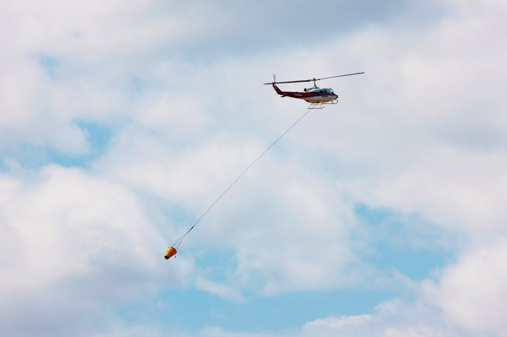 Stock Photo: 4316-4474 Firefighting helicopter carrying a bucket of water to a raging mountain wildfire, Colorado, USA