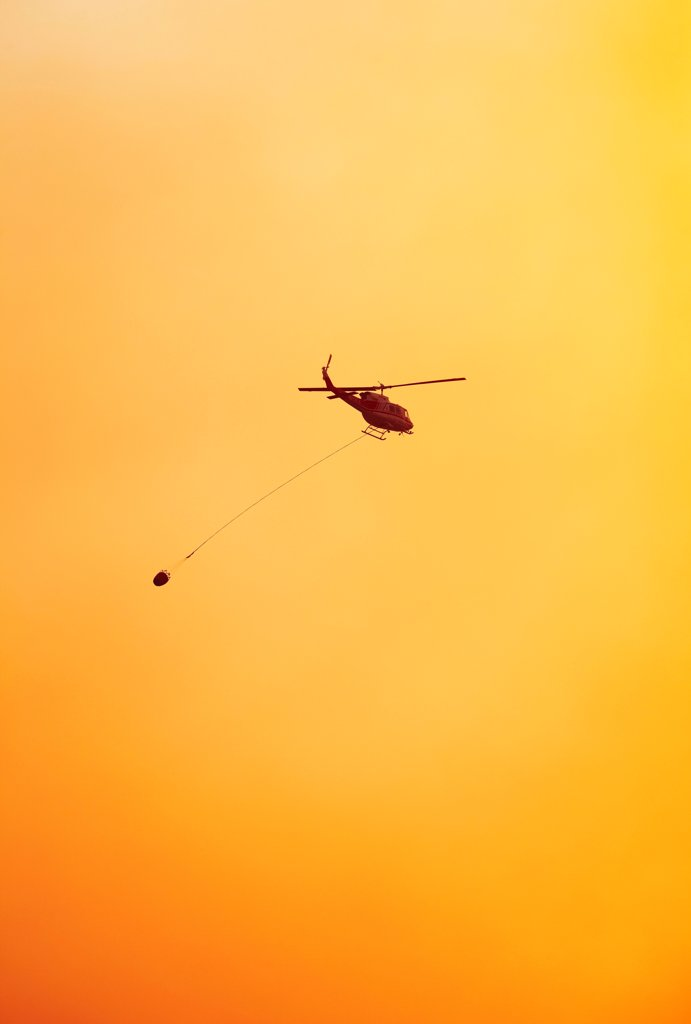 Stock Photo: 4316-4478 Firefighting helicopter carrying a bucket of water to a raging mountain wildfire, Colorado, USA