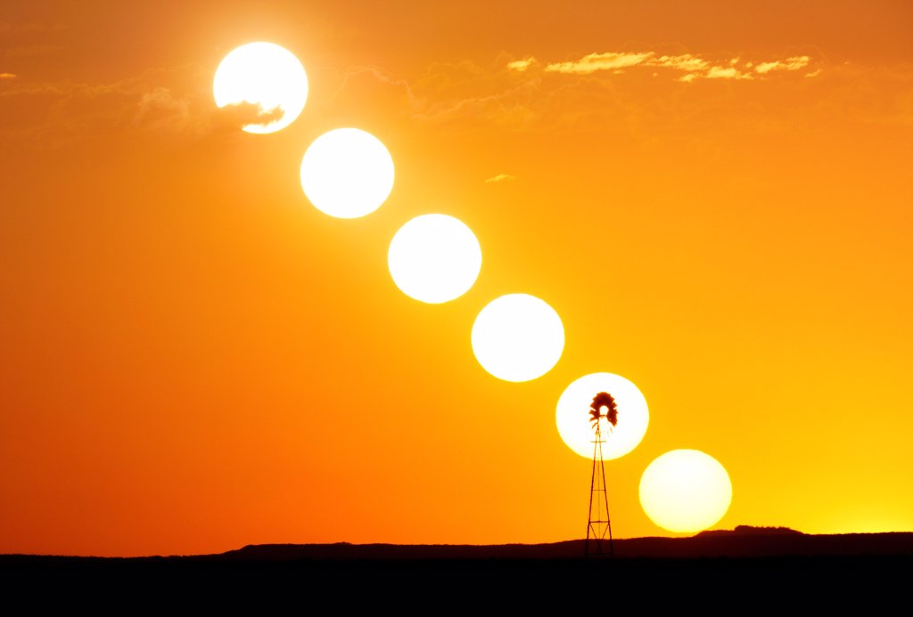 Sequence of the sun setting, silhouetting a lone windmill on plains, Colorado, USA : Stock Photo
