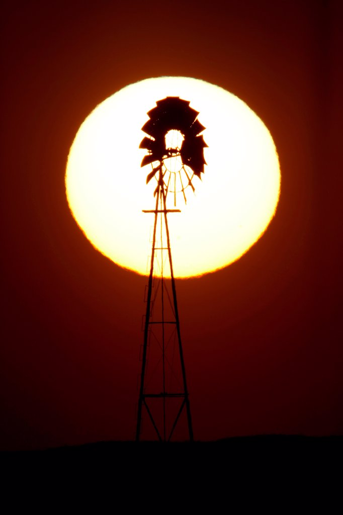 Stock Photo: 4316-4548 Setting sun silhouettes windmill on eastern plains of Colorado, USA
