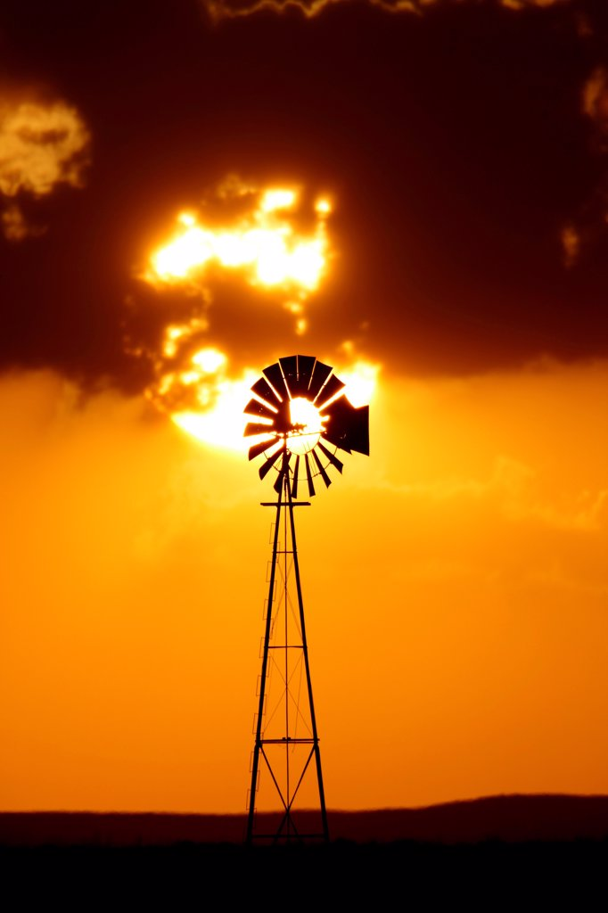 Stock Photo: 4316-4571 Telephoto view of setting sun and lone windmill