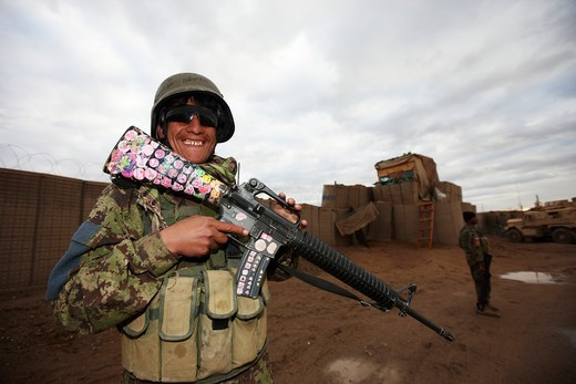 Afghan National Army Soldier shows off his M-16 which is adorned with childish stickers : Stock Photo