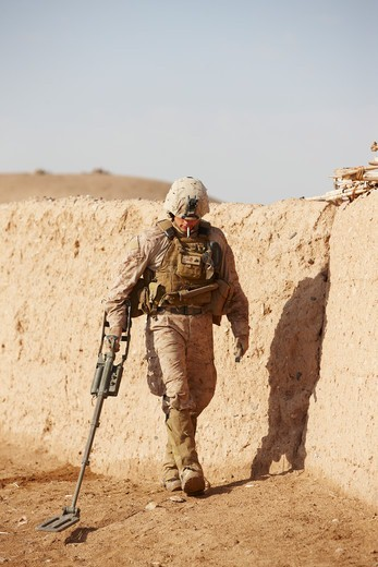 Stock Photo: 4316-4725 United States Marine combat engineer uses a metal detector to sweep for hidden explosives and weapons caches during a combat operation in Afghanistan's Helmand Province