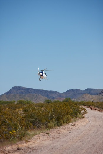 Stock Photo: 4316-4856 Border patrol helicopter flying low over the United States - Mexico border in southern Arizona