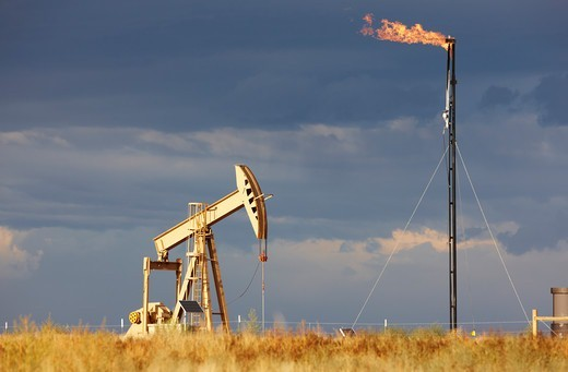 Stock Photo: 4316-5003 An Oil Well Pump Jack and Natural Gas Flare Tower