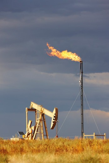 Stock Photo: 4316-5004 An Oil Well Pump Jack and Natural Gas Flare Tower