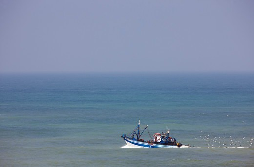 Stock Photo: 4316-5218 Fishing boat embarks into the Atlantic Ocean from the port at Tarfaya, in southern Morocco