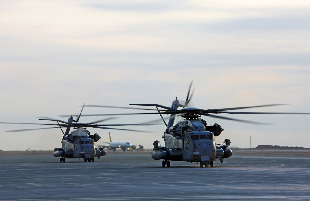 Stock Photo: 4316-5545 Two United States Marine Corps CH-53E Super Stallion helicopters refuel prepare to launch into the skies on a mission, Camp Bastion, Helmand Province, Afghanistan