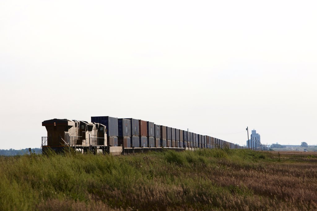 USA, Kansas, Freight Train, distant grain elevator : Stock Photo