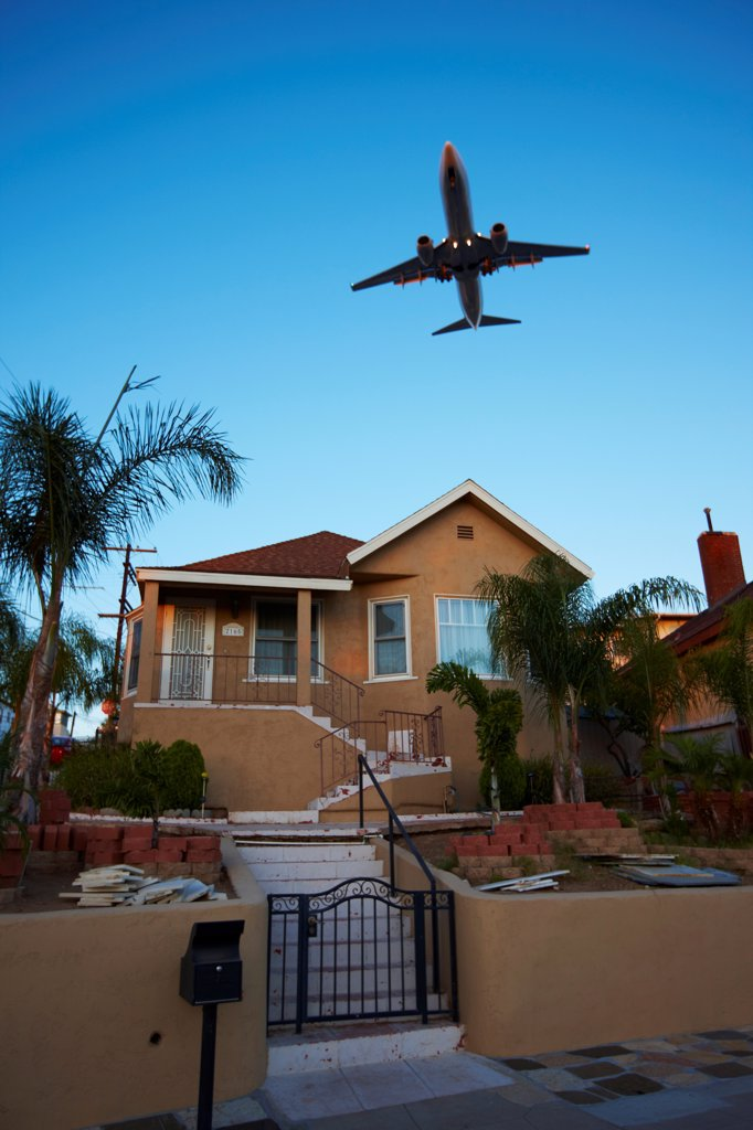 Stock Photo: 4316-5798 USA, California, San Diego, Jet airliner flying low over house