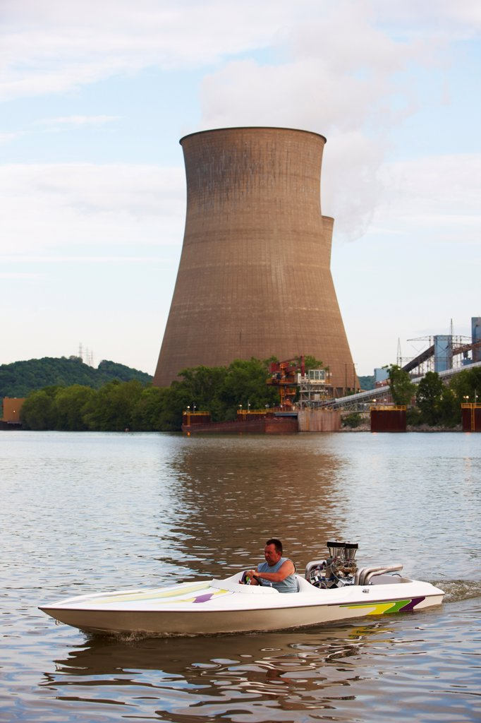 Stock Photo: 4316-5968 USA, West Virginia, Poca, Man in speedboat beneath cooling towers of John E. Amos Power Plant