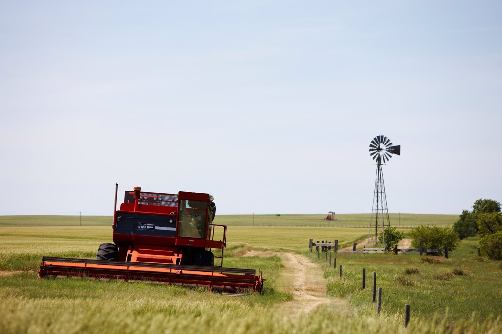 Stock Photo: 4316-5988 USA, Kansas, Wheat combine and windmill on ranch