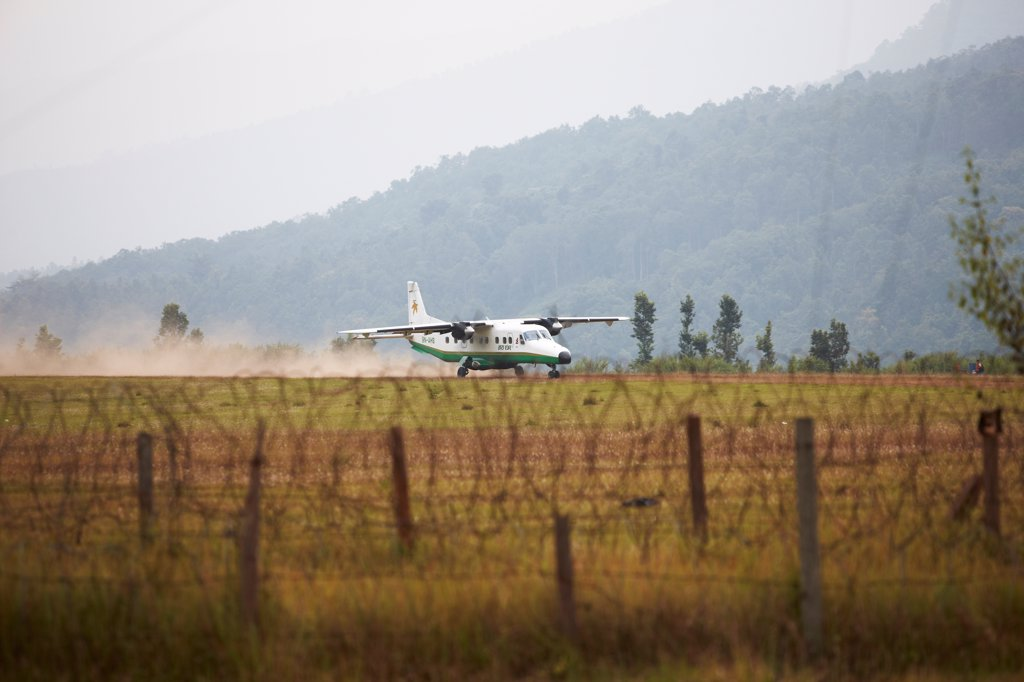 Nepal, Tumlingtar, Dornier Do 228, carrying passengers, landing on dirt runway : Stock Photo