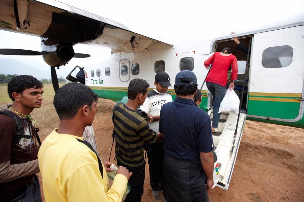 Nepal, Tumlingtar, passengers boarding into twin-turboprop aircraft at rural airstrip : Stock Photo