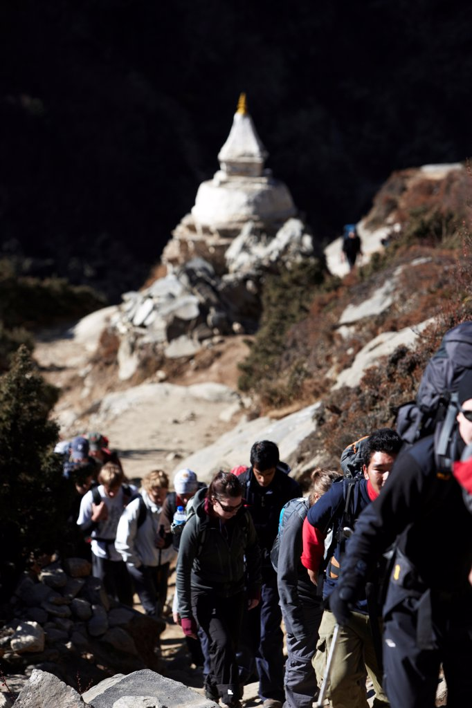 Nepal, Himalaya, Solukhumbu District, Khumbu, line of trekkers and Nepalese Sherpa porters passing Tibetan Buddhist Stupa : Stock Photo