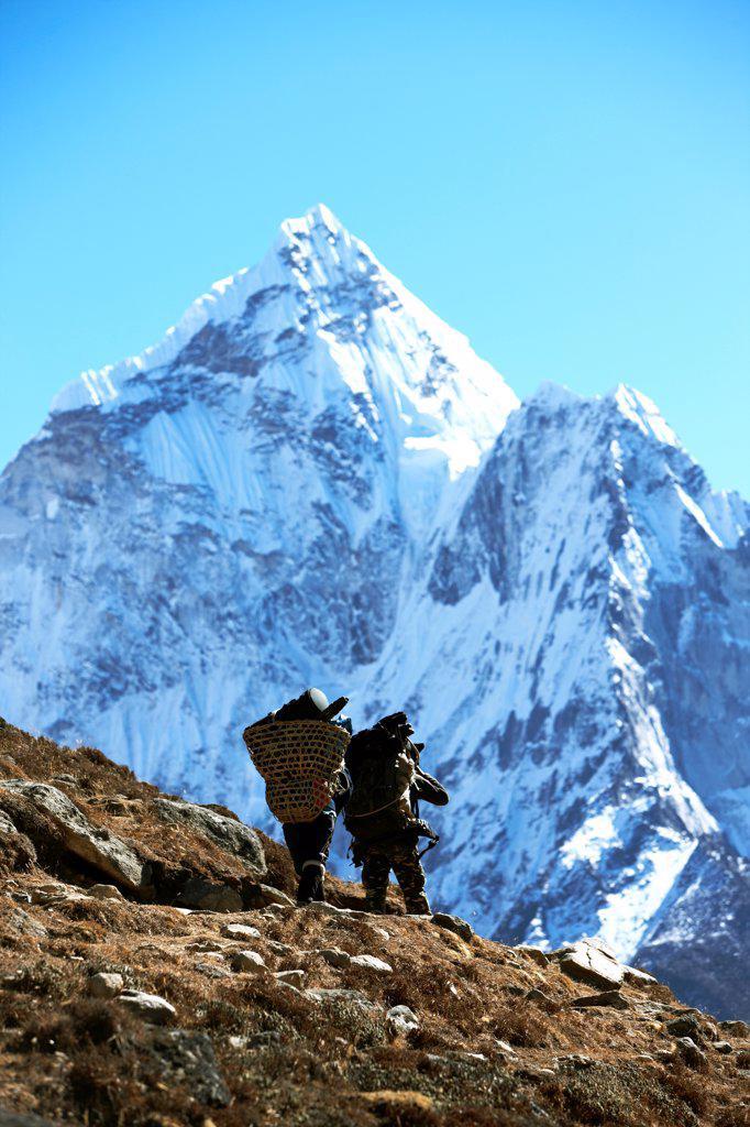 Stock Photo: 4316-6307 Nepal, Himalaya, Solukhumbu District, Khumbu, Sherpa porters beneath Ama Dablam, rear view