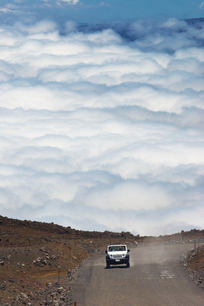 Jeep ascends the unpaved section of the John A. Burns Way near the summit of Mauna Kea, Hawaii County, Hawaii, USA : Stock Photo