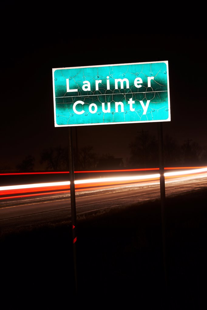 Stock Photo: 4316-7107 Larimer County sign on Colorado State Highway 14 at night, Colorado, USA