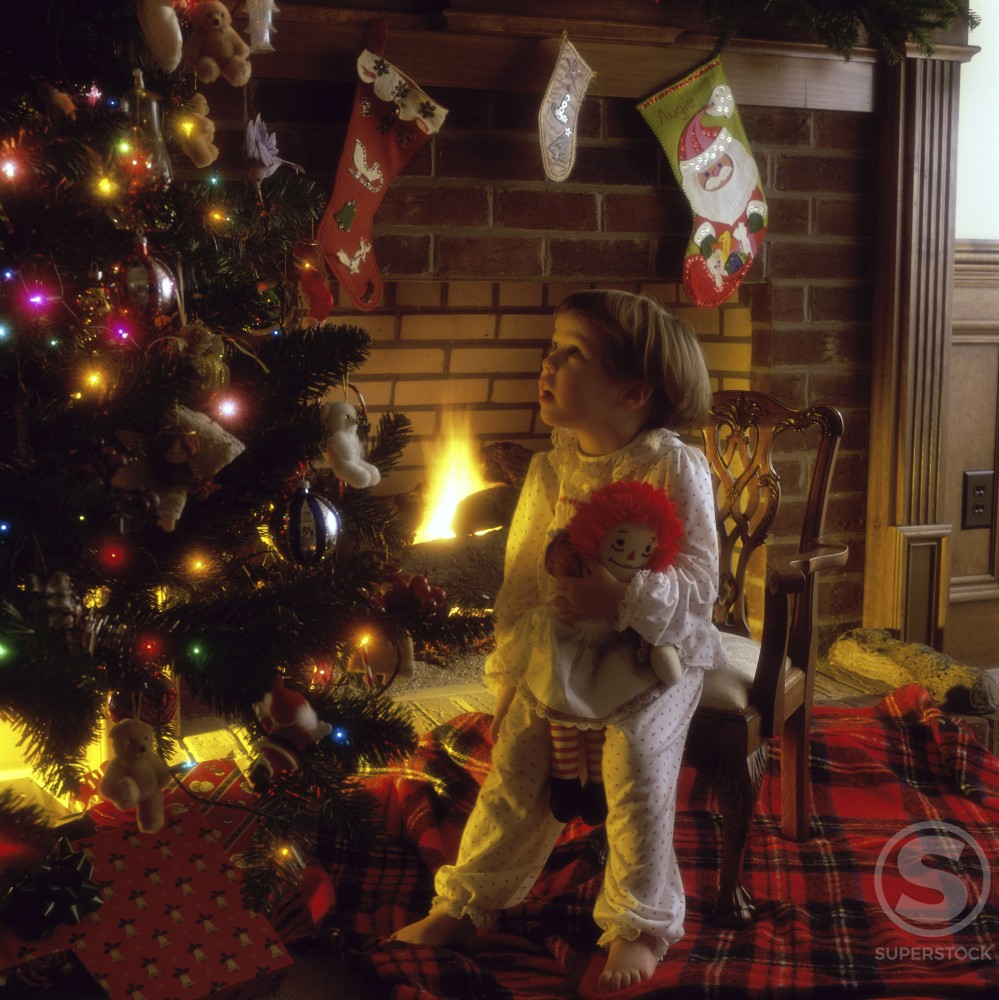 Stock Photo: 433-119 Girl holding a doll and looking at a Christmas tree