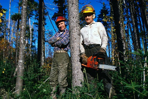 Two lumberjacks leaning against a tree, Oregon, USA : Stock Photo