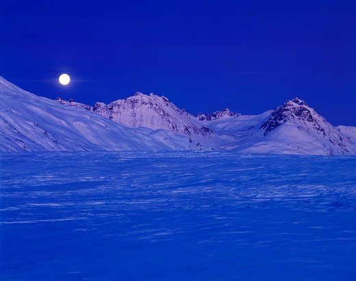 Full moon rising over a wintry Kusawak Range, Northern British Columbia, Canada. : Stock Photo