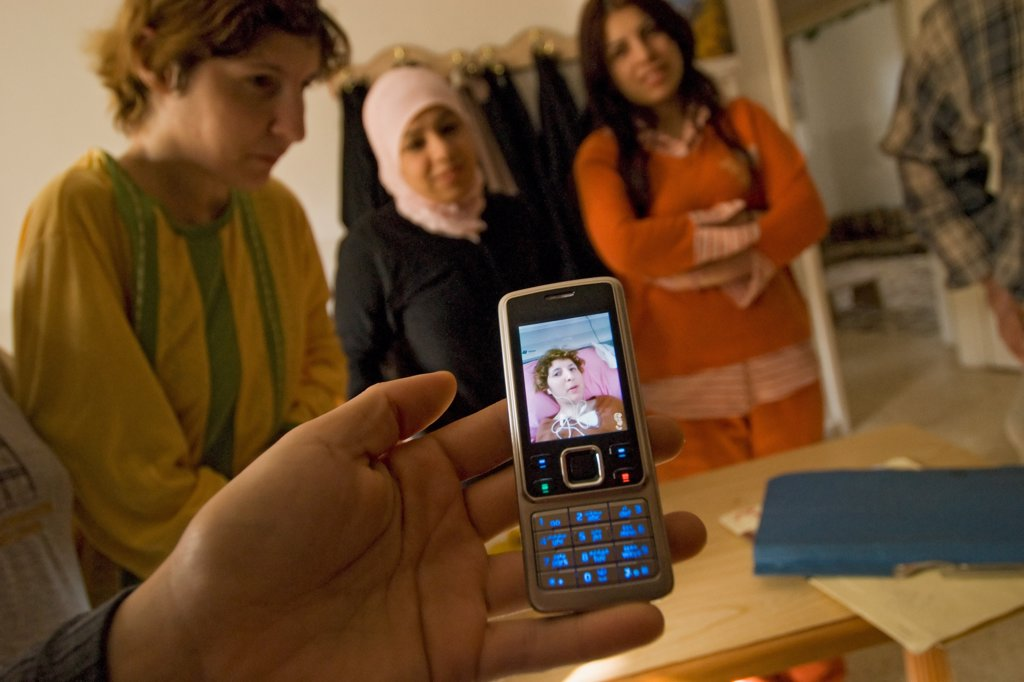 A Palestinian nurse in Amman, Jordan uses a cellphone to send pictures of a patient to a doctor for additional opinion. : Stock Photo
