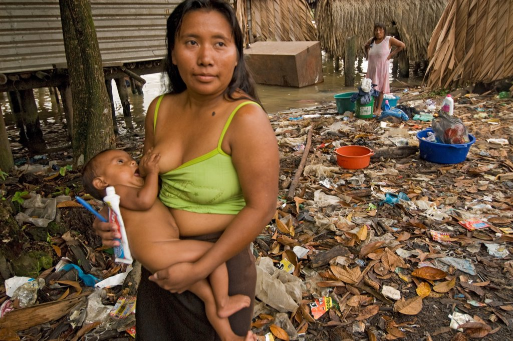 Stock Photo: 4339-1143 A Warao woman and child at a trash laden village on the shores of the Orinoco River in Venezuela.  Most Warao women have a number of babies but infant mortality is high and female life expectancy is low. Diarrhea and other water born diseases as well as parasites contribute to health issues.