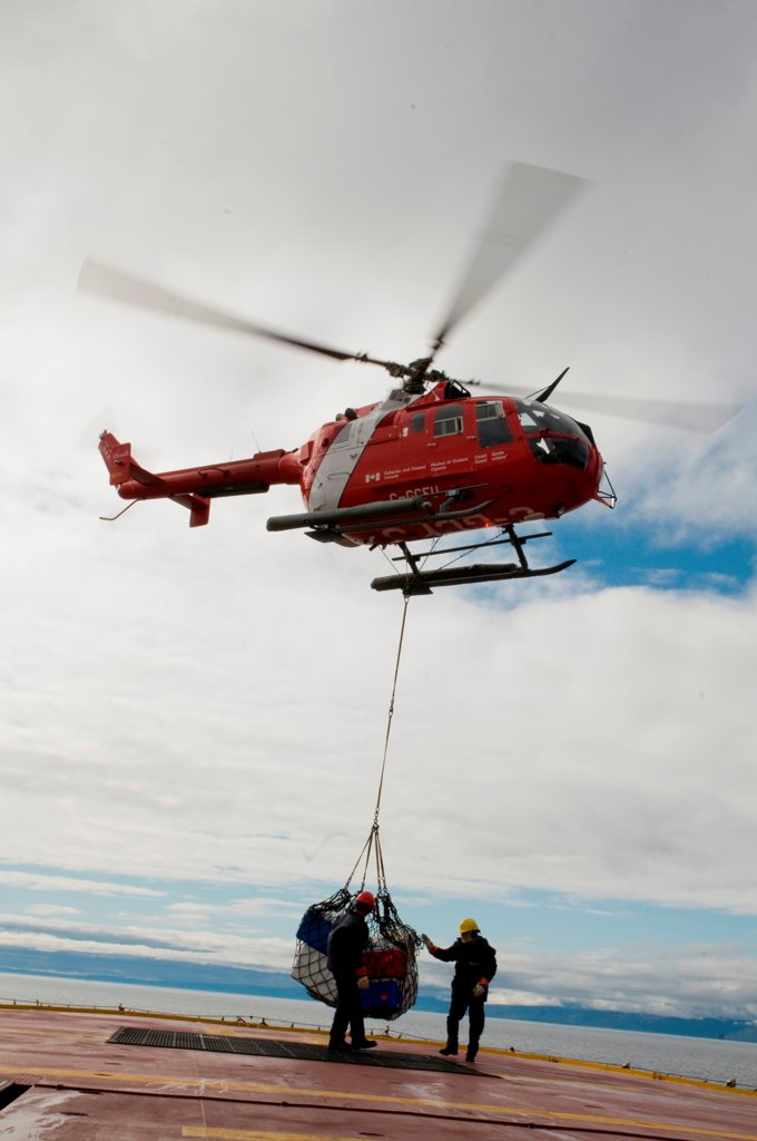 Stock Photo: 4340-2498 Canadian coast guard helicopter brings new crew members, researchers, and gear, aboard the CCGS Amundsen, a coast guard ship where scientific research is conducted, Iqualuit, Baffin Island, Nunavut, Canada