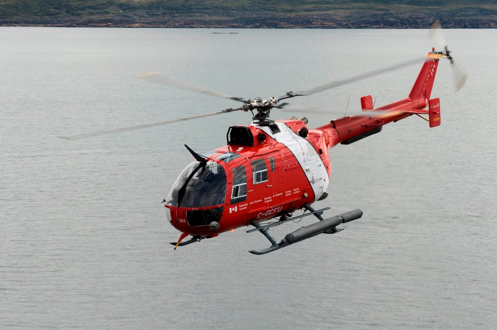 Canadian coast guard helicopter transporting crew members, researchers, and gear aboard the CCGS Amundsen, a coast guard ship where scientific research is conducted, Iqualuit, Nunavut Territory, Canada : Stock Photo