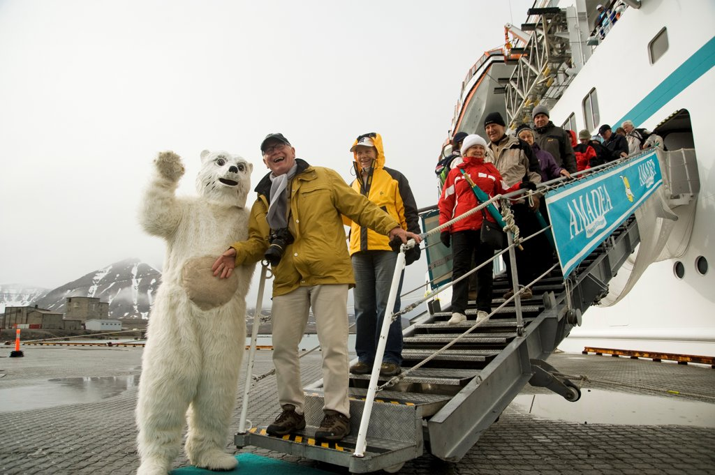 Norway, Svalbard Archipelago, Spitsbergen, Ny Alesund, Passengers disembarking from cruise ship posing with costumed Polar bear : Stock Photo