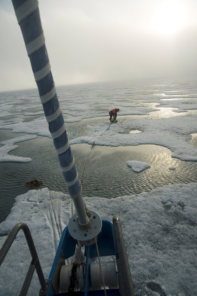 Stock Photo: 4340-2829 Norway, Svalbard Archipelago, Sailboat captain dropping anchor in fjord ice along northwest coast of Spitsbergen