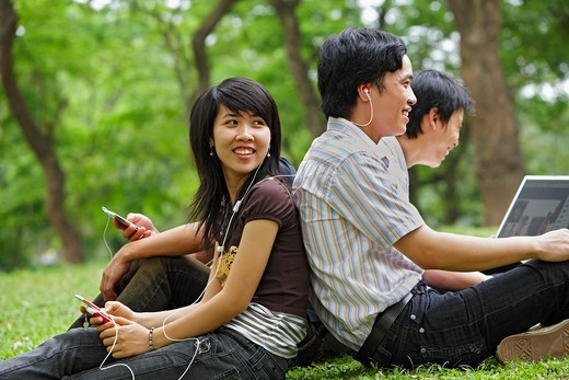 Stock Photo: 4347-297 A group of four young Vietnamese are sitting in the park enjoying their modern electronic devices such as MP3 players, cellphones and laptops. They are laughing together.
