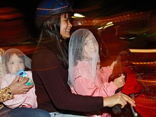 A Vietnamese family is driving through the night on their motorbike. One girl is standing in front of the mother holding the two rear-view mirrors. The other one is sitting in the back drinking milk. A fourth person is holding the little one. Hanoi, Vietnam. : Stock Photo