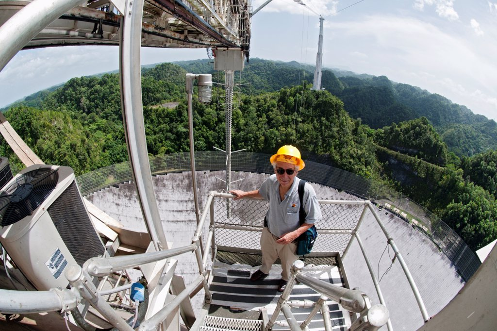 The Arecibo Observatory is a radio telescope just over 1,000 feet (305 m) across, the largest single radio telescope. The main metal collecting dish sits fixed a hemispherical karst sinkhole. Because it is fixed, a spherical reflector hangs 500 feet (150 m) over the dish on a 900 ton platform, known as 'the feed'. The observatory is the primary location of the National Astronomy and Ionosphere Center, NAIC. : Stock Photo
