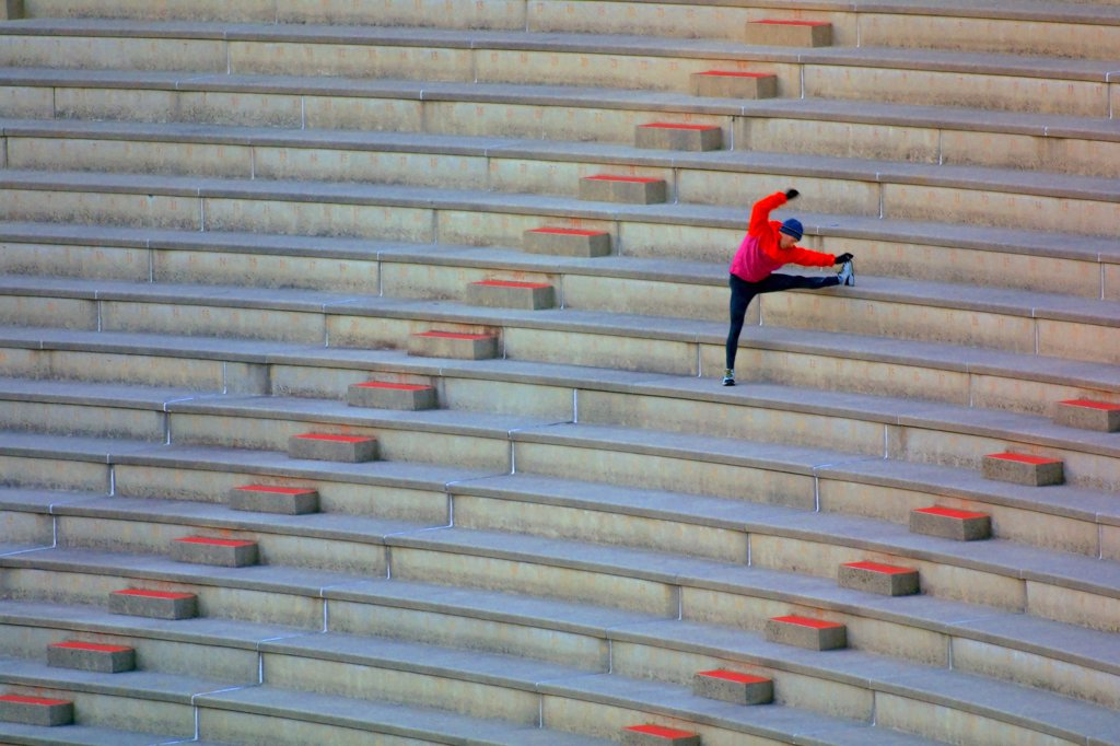An athlete stretching in the bleachers of a stadium, preparing to run up and down the steps. : Stock Photo