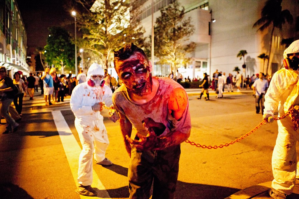 Stock Photo: 4355-1781 A man dressed as a zombie with haz-mat suited handlers in a Halloween event in Miami Beach.