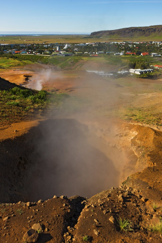 Stock Photo: 4355-1933 Steam emerging from vents and mudpots in Hverageroi, Iceland. Hverageroi is a small town in the south of Iceland located 45 km to the east of Reykjav?k, Iceland. A large earthquake on May 30, 2006 opened up the earth creating a series of vents and fumaroles of bubbling mud and steam.