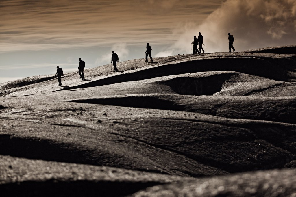 Hikers traverse the ash-blackened Vatnajokull Glacier. Black ash from volcanic eruptions darkens the ice at the Vatnajokull Glacier. Vatnajokull is the largest glacier in Iceland. It is located in the south-east of the island, covering more than 8% of the country. Vatnajokull is the largest ice cap in Europe. The average thickness of the ice is 400 meters, with a maximum thickness of 1,000 meters. : Stock Photo