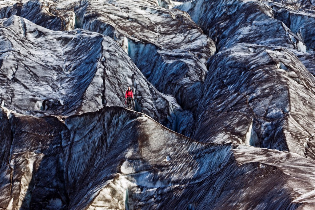 Stock Photo: 4355-1969 A hiker in dressed in red stands out on the ash-blackened Vatnajokull Glacier, Iceland