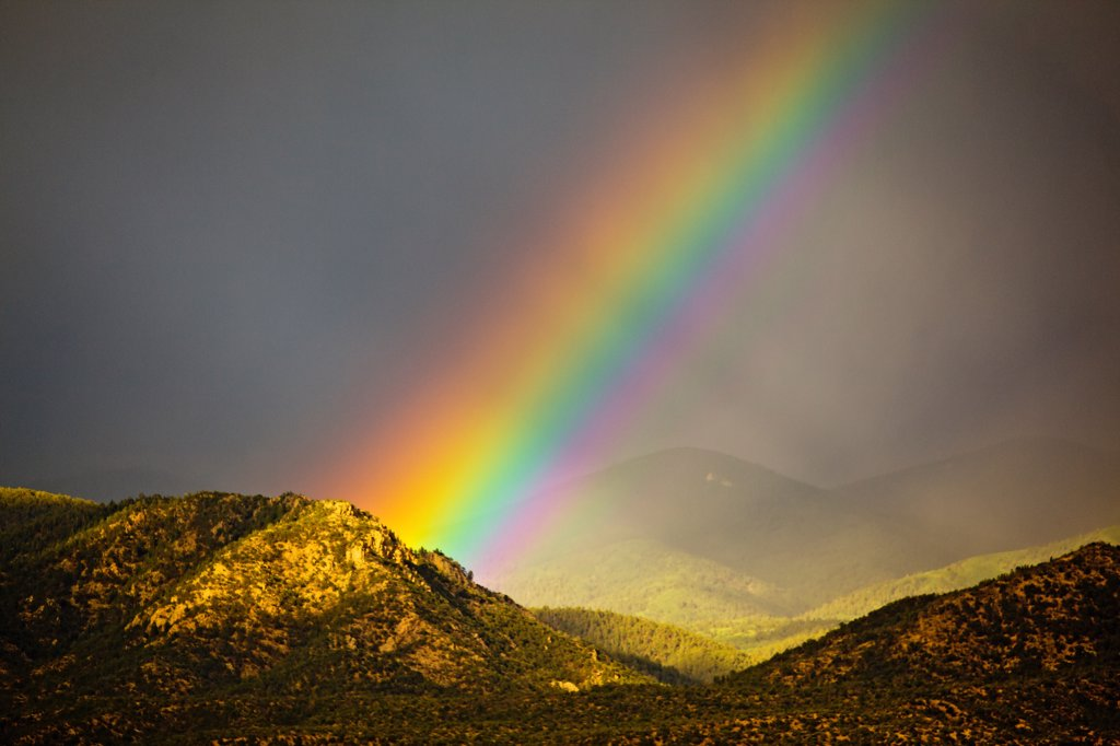 Stock Photo: 4355-2081 An enormous rainbow emanating from behind a sunlit mountain.