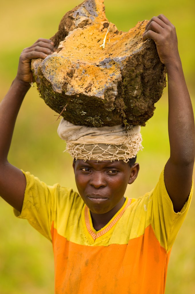 Rwanda, Gahilikiro, Young man carrying rock on his head : Stock Photo