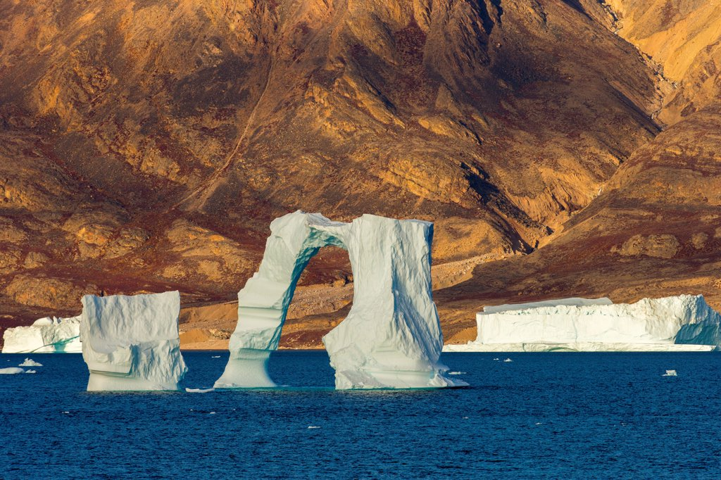 Stock Photo: 4355-2357 Greenland, Arched iceberg against rocky shore, distant view