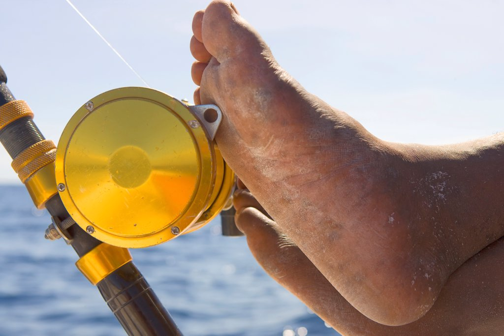 Feet on Fishing Reel : Stock Photo