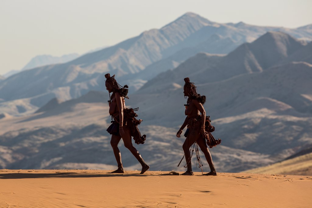Stock Photo: 4355-2388 Namibia, Serra Cafema, Two Himba woman walking with mountains in background